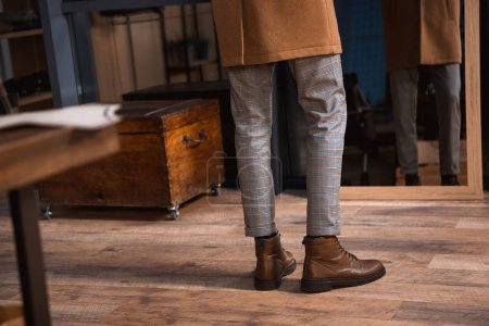 low section of man in leather boots and overcoat standing near mirror in boutique