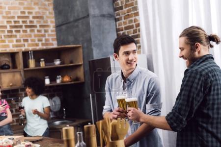 hommes tinter les verres de bière dans la cuisine