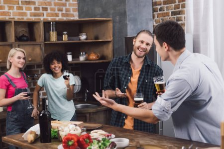 smiling multiethnic friends talking in kitchen with beer and wine