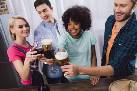 overhead view of multiethnic friends clinking with glasses of wine and beer