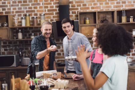 Photo pour Amis multiethniques jouer avec des œufs de poulet dans la cuisine - image libre de droit