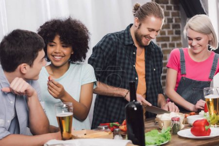 multiethnic friends cooking together in kitchen