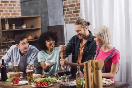 Photo for Multiethnic friends looking how man adding spice to food with pepper grinder - Royalty Free Image