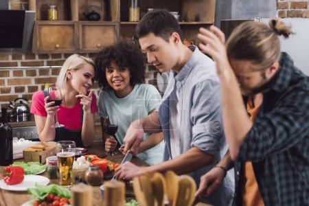 multiethnic girls drinking wine and looking at men cooking  in kitchen