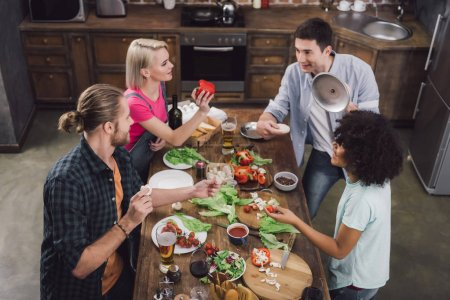 Photo for Overhead view of multicultural friends playing with food - Royalty Free Image