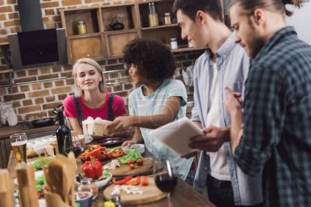 multiethnic friends searching recipe for food with tablet