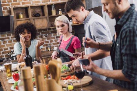 Foto de Chica africana americana hablando por teléfono inteligente mientras amigos de cocina - Imagen libre de derechos