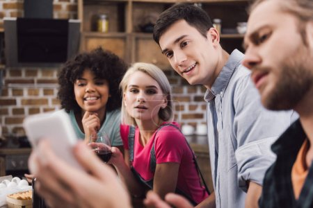 multiethnic friends looking at smartphone in kitchen