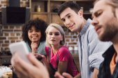 multiethnic friends looking at smartphone in kitchen