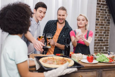 caucasian girl taking photo of african american friends pizza with smartphone