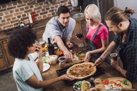 Photo for Multicultural friends eating homemade pizza in kitchen - Royalty Free Image
