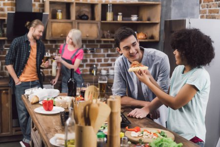 Photo for Multicultural friends eating homemade pizza and drinking alcohol at home - Royalty Free Image