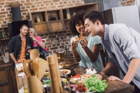 girl feeding friend with piece of pizza in kitchen