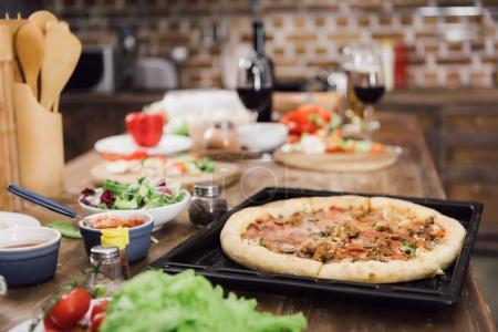 homemade delicious pizza on table in kitchen