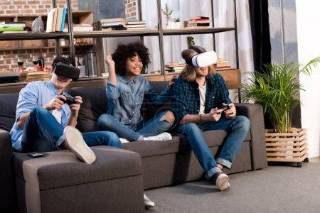 Photo for Multicultural friends playing video game with virtual reality headsets - Royalty Free Image