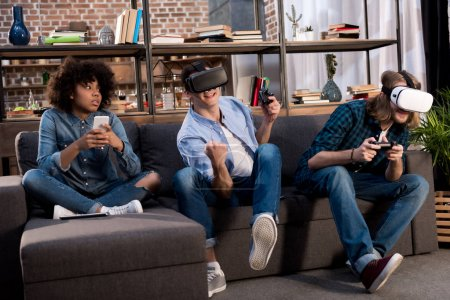 Photo for Friends playing video game with virtual reality headsets, african american girl sitting with smartphone - Royalty Free Image