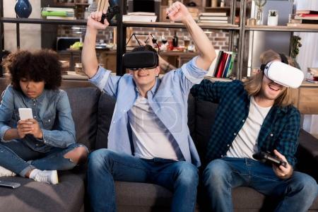 Foto de Amigos que juegan videojuegos con auriculares de realidad virtual - Imagen libre de derechos