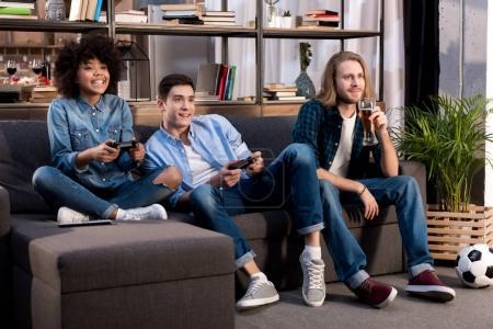 Foto de Amigos multiculturales jugando videojuegos en sofá en casa - Imagen libre de derechos