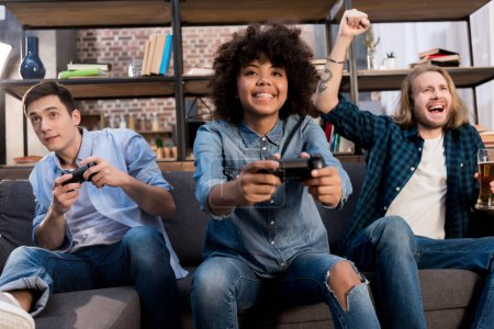 Photo for Multicultural friends playing video game on sofa at home - Royalty Free Image