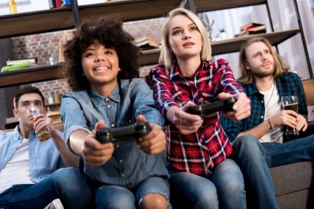 Photo for Multicultural girls playing video game on sofa at home, men drinking beer - Royalty Free Image