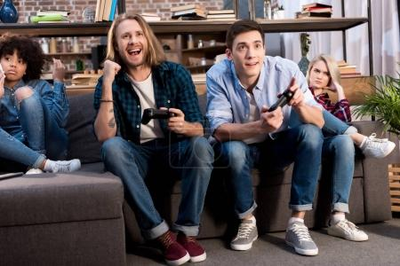 Photo for Men playing video game and multicultural girls sitting upset - Royalty Free Image