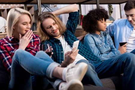 multicultural friends sitting on sofa and looking at smartphone