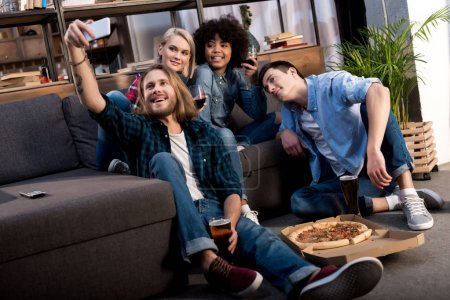 multicultural friends taking selfie on sofa at home