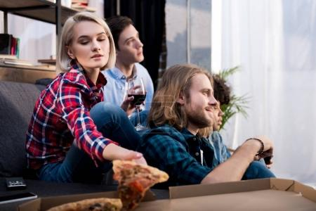 girl taking piece of pizza while spending time with friends
