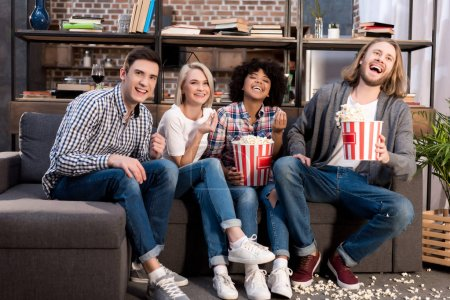 laughing multicultural friends watching tv on sofa with popcorn
