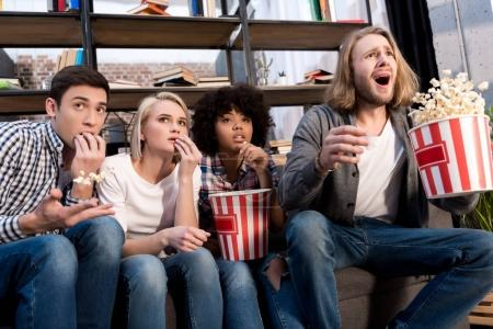 Shocked multicultural friends watching film with popcorn