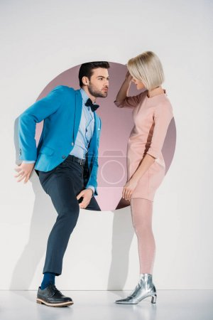fashionable couple in love looking at each other while stepping through hole on grey