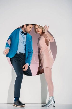 Photo for Fashionable couple in love stepping through hole on grey - Royalty Free Image