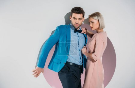 fashionable young couple posing together in hole on grey