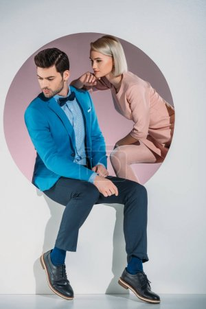 stylish young couple looking away while sitting together in aperture on grey