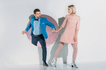 young couple in suit and dress holding hands and looking at each other on grey