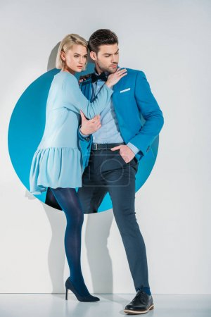Photo for Fashionable young couple stepping from blue hole on grey - Royalty Free Image