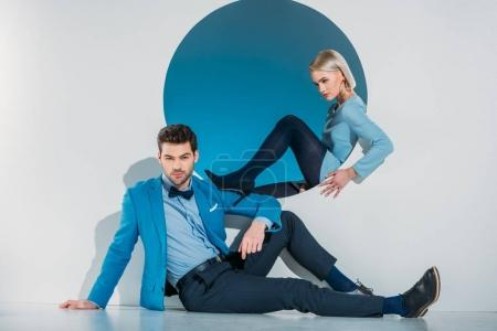beautiful stylish young couple in blue suit and dress sitting near opening on grey
