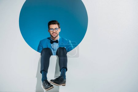 stylish young man smiling at camera while falling into hole on grey