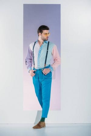 handsome stylish young man in suspenders and eyeglasses looking away while standing in opening on grey