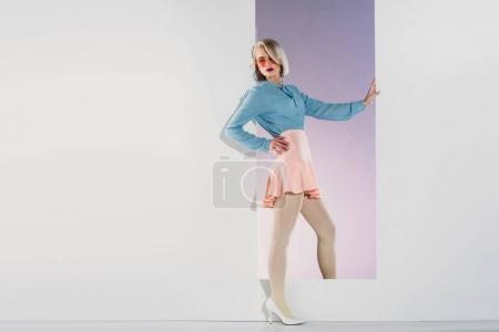 beautiful fashionable young blonde woman posing in opening on grey