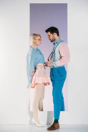 fashionable young couple in eyeglasses looking at each other while standing in aperture on grey