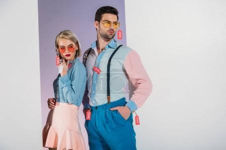 Photo pour Élégant jeune couple avec des étiquettes de vente sur les vêtements debout dans l'ouverture sur gris - image libre de droit