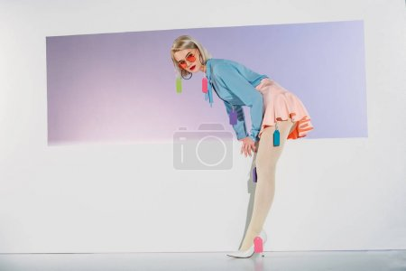beautiful blonde girl with colorful blank tags on clothes stepping through aperture on grey