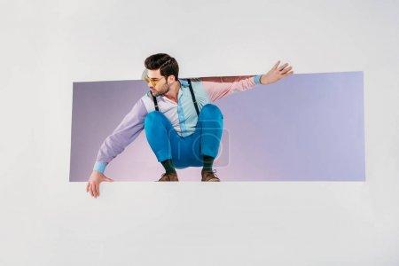 Photo pour Beau jeune élégant homme accroupi en ouverture et en regardant loin sur fond gris - image libre de droit