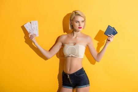 beautiful young blonde woman in denim shorts and top holding passports and tickets on yellow
