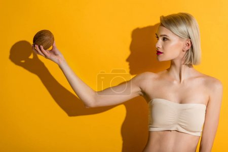beautiful young blonde woman in top holding coconut on yellow