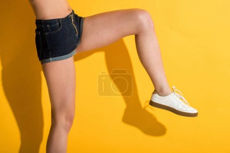 cropped shot of girl in denim shorts posing on yellow
