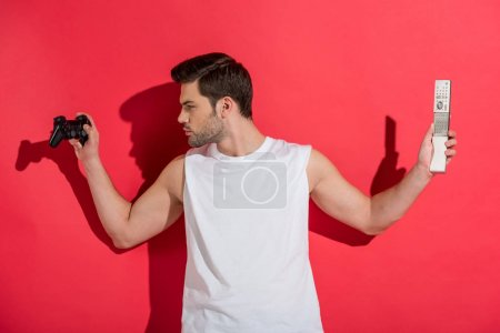 handsome young man holding gamepad and remote controller on pink