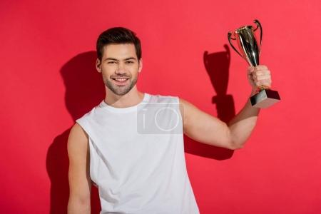 handsome young man holding trophy and smiling at camera on pink