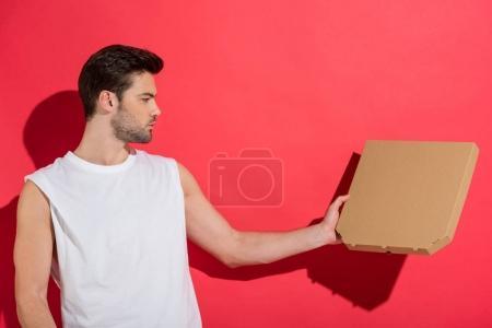 schöner junger Mann mit leerer Pizzakiste auf rosa